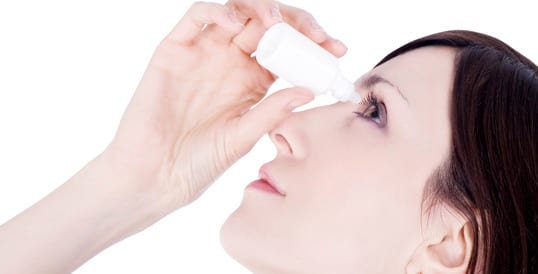 Woman using eye drops to combat winter dry eyes
