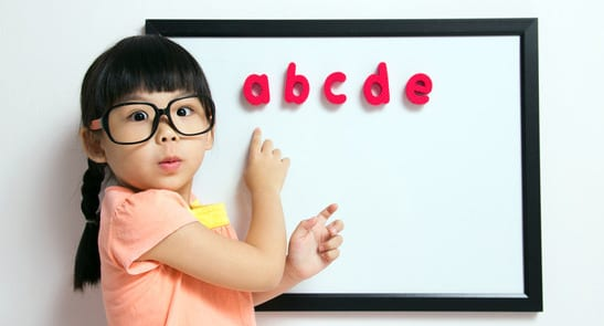 Child wearing glasses at whiteboard
