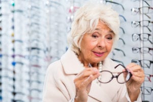 Senior woman trying on eyeglasses